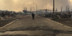Lone RCMP officer surveys damage of Ft. McMurray fire. Photo credit: Alberta RCMP